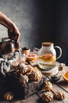 Saborosos bolos com chá quente com fatias de toranja fresca na mesa de madeira. bebida saudável, ecológica, vegana