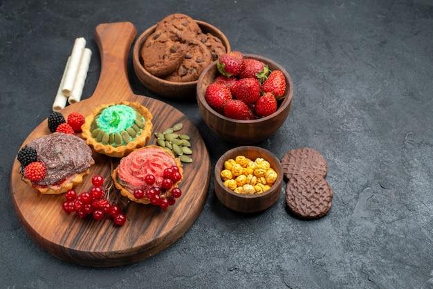 Saborosos bolos cremosos de vista frontal com biscoitos e frutas em fundo escuro