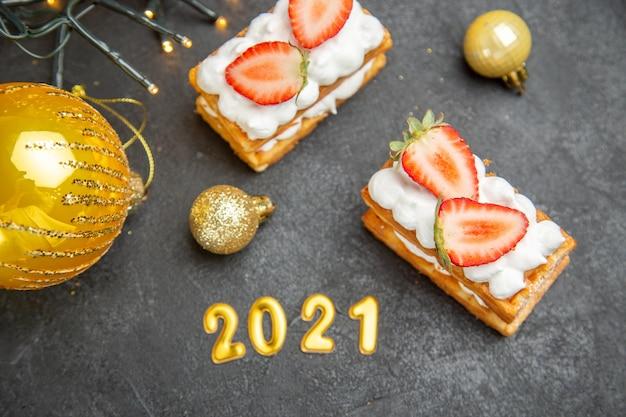 Saborosos bolos de creme com morangos ao redor de brinquedos de árvore de ano novo em fundo escuro, vista de cima
