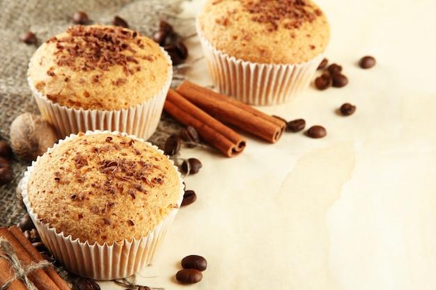 Saborosos bolos de muffin com chocolate, especiarias e sementes de café, em superfície bege