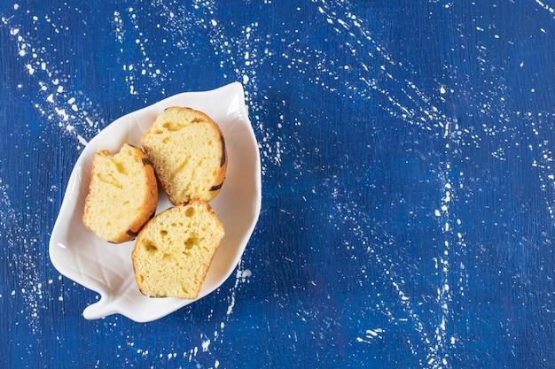 Saborosos bolos fatiados frescos colocados em um prato em forma de folha