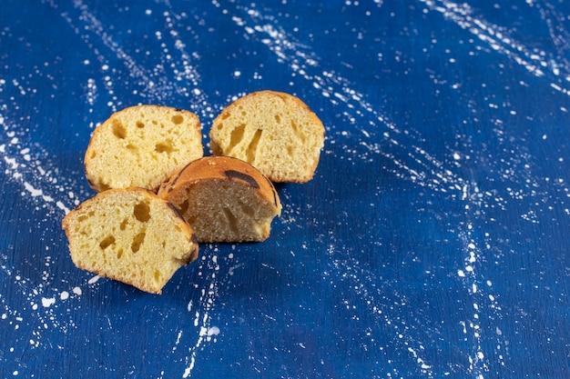 Saborosos bolos fatiados frescos colocados na mesa de mármore.