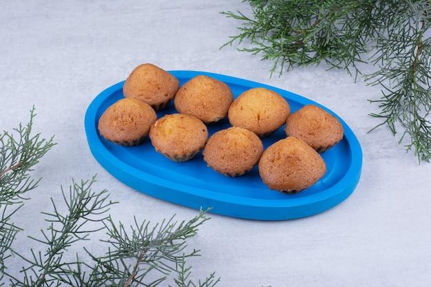 Saborosos bolos pequenos na placa azul com galho de pinheiro.
