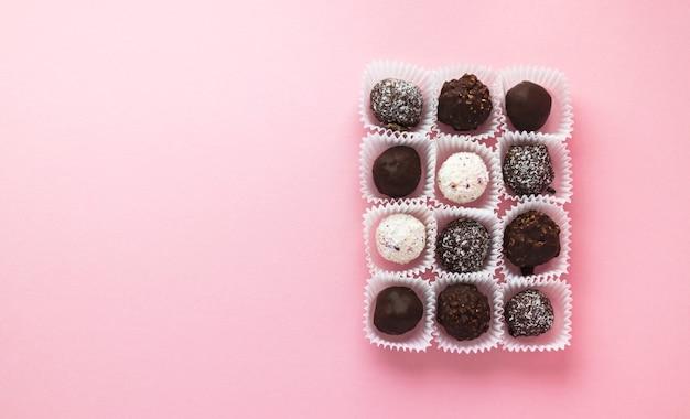 Saborosos bombons de chocolate em forma de bola embalados em pequenas cestas de papel sobre fundo rosa. sobremesa romântica do dia dos namorados. doce delicioso. estilo mínimo. camada plana, vista de cima com cópia em cena.