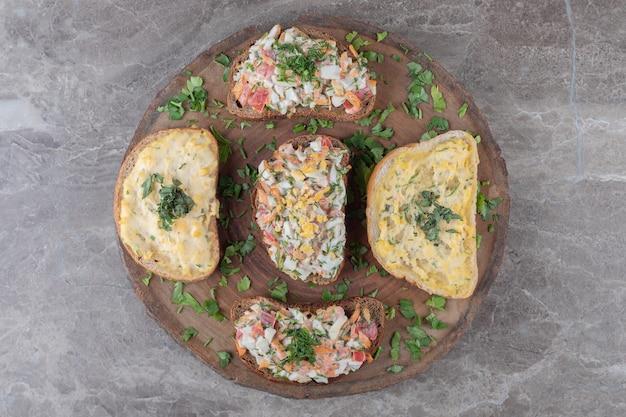Saborosos bruschettas com ovos e vegetais na peça de madeira.