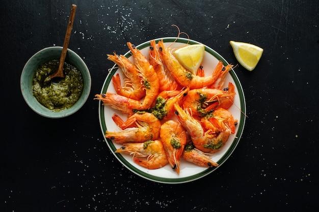 Saborosos camarões com especiarias e molho no prato na superfície escura
