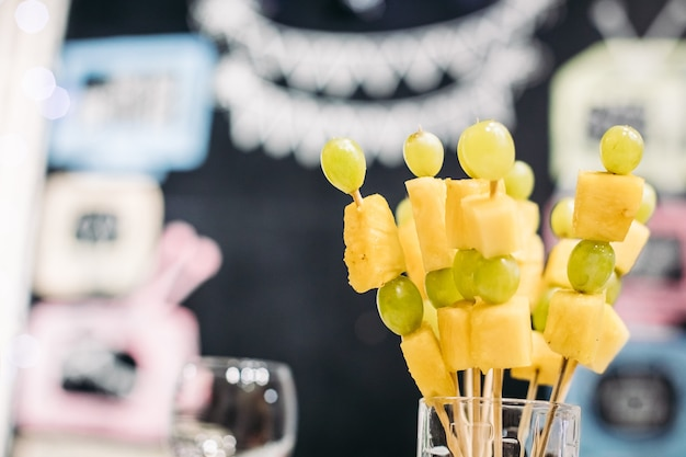 Saborosos canapés com queijo e uvas verdes em vidro na festa no fundo desfocado. lanches de festa e conceito de comida.