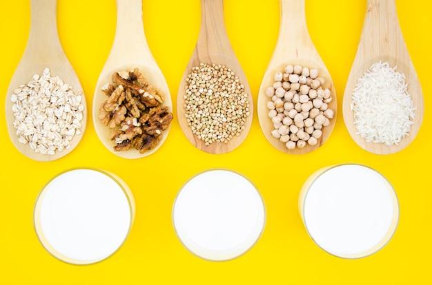 Saborosos cereais e nozes em colheres de madeira com leite