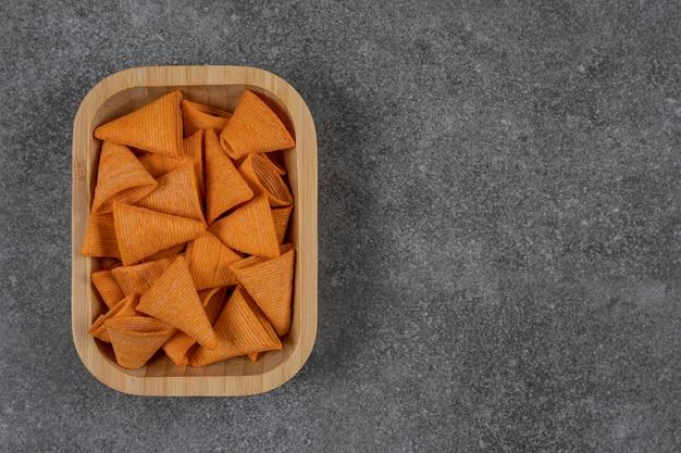 Saborosos chips crocantes na placa de madeira.