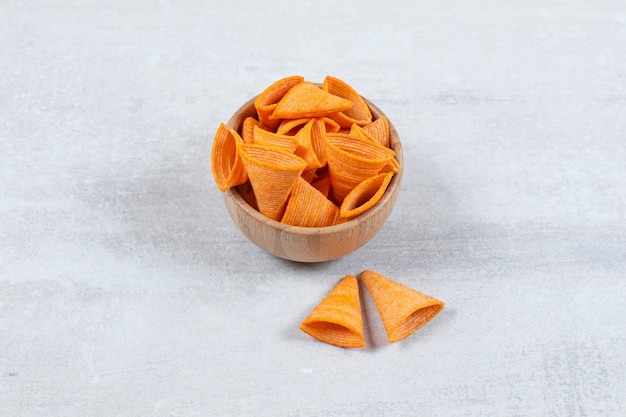 Saborosos chips de triângulo em uma tigela de madeira.