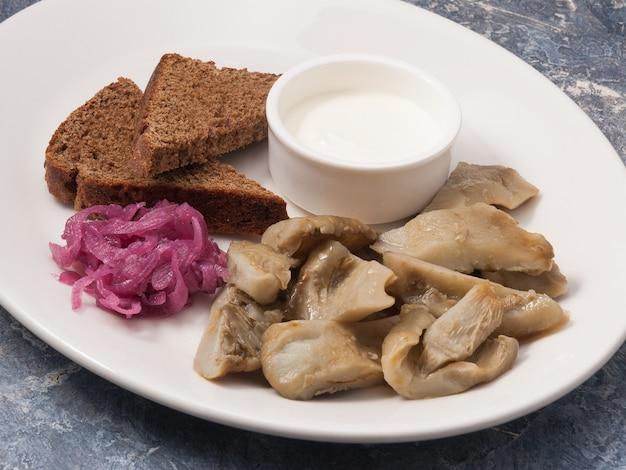 Saborosos cogumelos salgados com creme azedo de pão de centeio e cebolas vermelhas