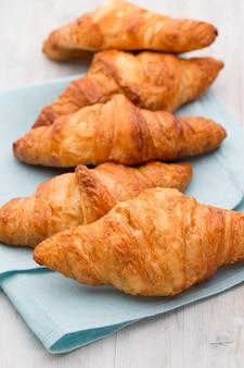 Saborosos croissants amanteigados na velha mesa de madeira.