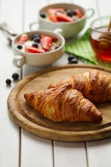 Saborosos croissants bonitos na placa de madeira. pequeno-almoço continental tradicional. granola com frutas e mel no fundo.