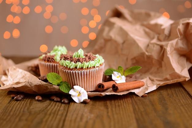 Saborosos cupcakes com creme de manteiga, na mesa de madeira, com luzes de fundo