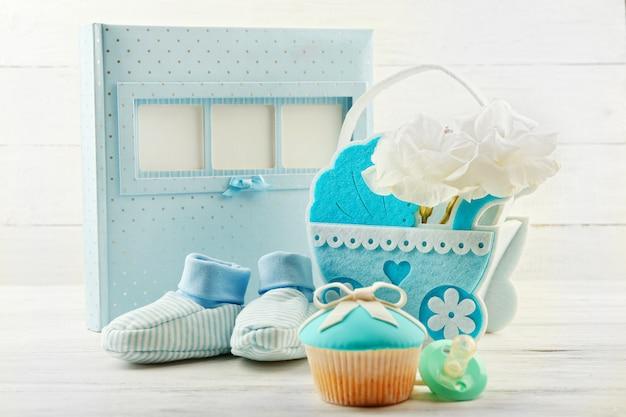 Saborosos cupcakes com laço e sapatos de bebê, carrinho de bebê decorativo e álbum de fotos com fundo colorido