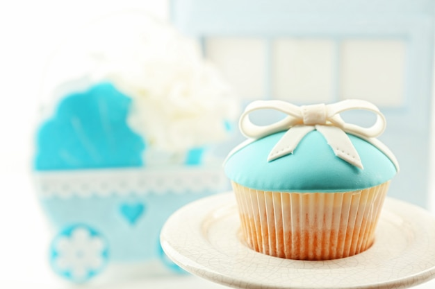 Saborosos cupcakes com laço e sapatos de bebê, carrinho de bebê decorativo na superfície colorida