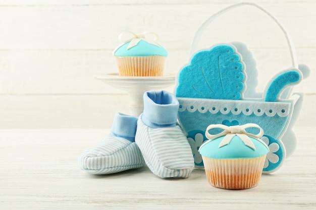 Saborosos cupcakes com laço e sapatos de bebê, carrinho de bebê decorativo