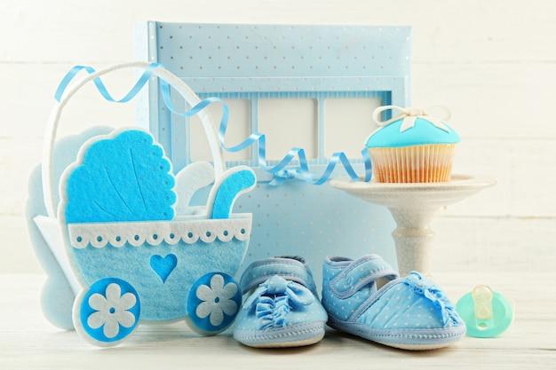 Saborosos cupcakes com laço e sapatos de bebê decorativos, carrinho de bebê e álbum de fotos na cor de fundo