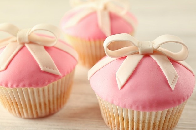Saborosos cupcakes com laço, em fundo claro