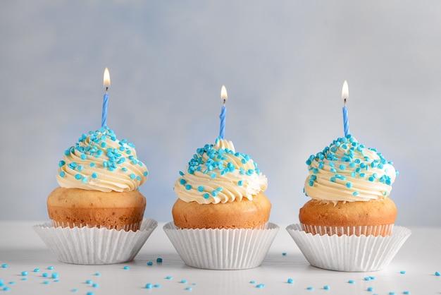 Saborosos cupcakes de aniversário na mesa branca