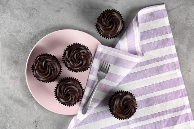 Saborosos cupcakes de chocolate na mesa cinza