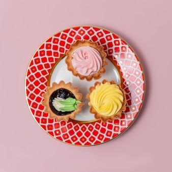 Saborosos cupcakes na placa vermelha padrão. três diferentes cupcakes com creme rosa e amarelo. deliciosa sobremesa natural caseira.