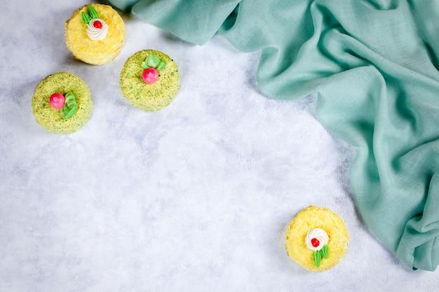 Saborosos, deliciosos, coloridos bolos com decoração na mesa de madeira, plana leigos