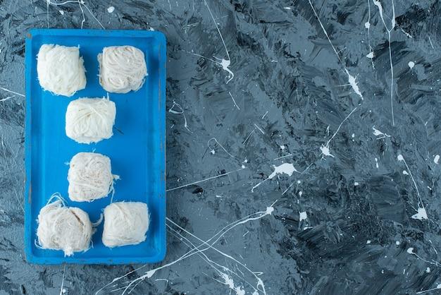 Saborosos doces de algodão turco em uma placa de madeira, na mesa azul.