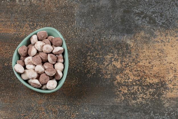 Saborosos doces marrons em uma tigela azul.