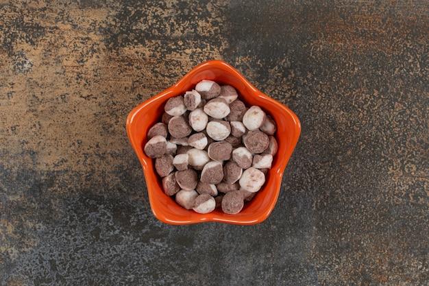 Saborosos doces marrons em uma tigela de laranja.
