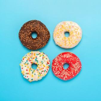 Saborosos donuts de diferentes tipos em um espaço azul. conceito de doces, pastelaria, pastelaria. quadrado. camada plana, vista superior.