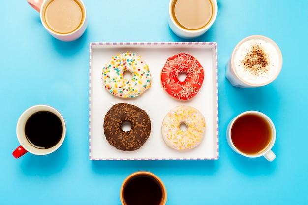Saborosos donuts e xícaras com bebidas quentes, café, cappuccino, chá
