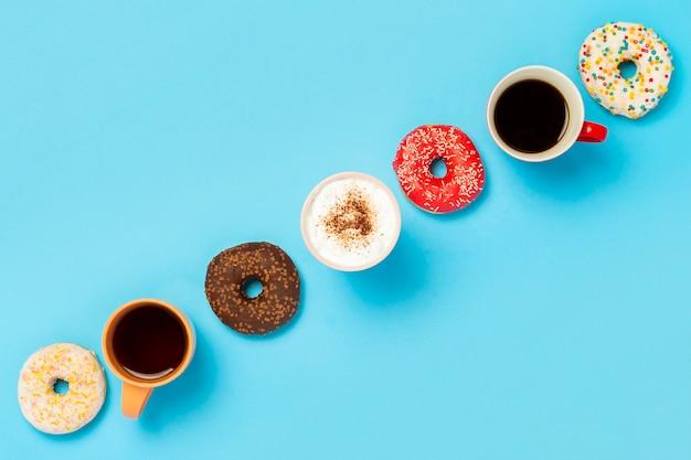 Saborosos donuts e xícaras com bebidas quentes, café, cappuccino, vista superior do chá