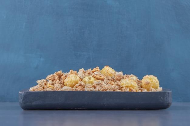 Saborosos flocos de milho em uma placa, na mesa de mármore.