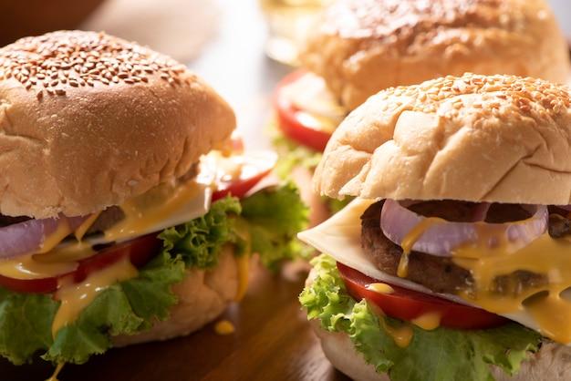 Saborosos hambúrgueres caseiros grelhados com carne, tomate, queijo, pepino e alface