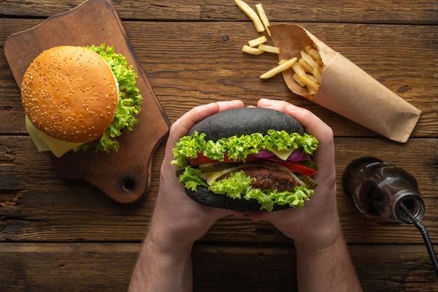 Saborosos hambúrgueres frescos com batatas fritas, beba na vista de cima da mesa de madeira.