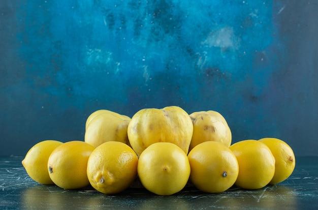 Saborosos marmelos e limões na mesa de mármore.