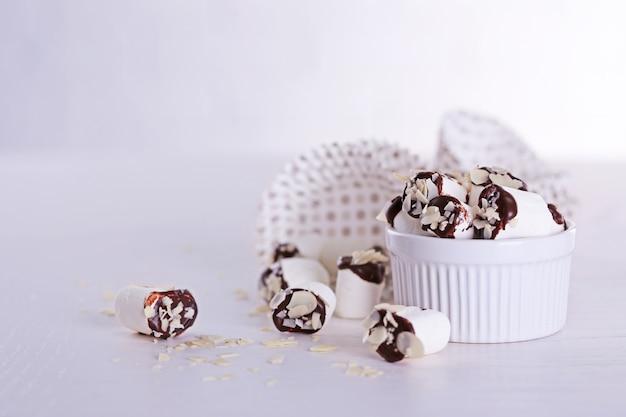Saborosos marshmallows com chocolate em uma tigela na mesa, close-up