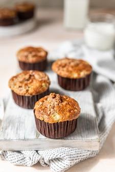 Saborosos muffins de café da manhã com migalhas de aveia cobrindo a superfície de concreto leve da placa de corte branca