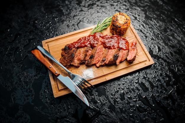 Saborosos pedaços de carne grelhada picada e servida na placa de madeira