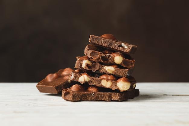 Saborosos pedaços de chocolate na mesa de madeira branca