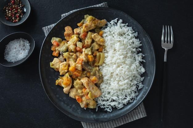 Saborosos pedaços de frango cozido com legumes e arroz servidos no prato. vista do topo