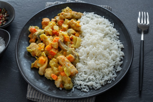 Saborosos pedaços de frango cozido de outono com legumes e arroz servidos no prato. vista do topo