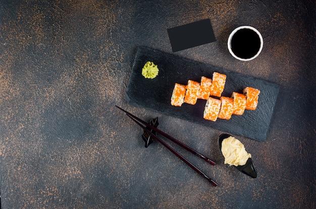 Saborosos rolinhos da califórnia e maki em um prato de pedra com molhos, pauzinhos, gengibre e wasabi