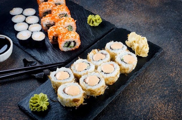 Saborosos rolos de sushi e maki em um prato de pedra com molhos, pauzinhos, gengibre e wasabi