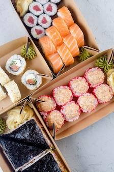 Saborosos rolos de sushi em caixas descartáveis de papel kraft, molho concept delivery service
