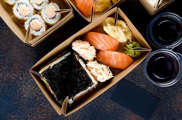 Saborosos rolos de sushi em caixas descartáveis de papel kraft, molhos