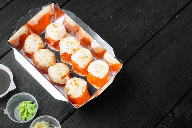 Saborosos rolos de sushi em caixas descartáveis, em mesa de madeira preta