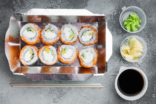 Saborosos rolos de sushi em caixas descartáveis fixadas em pedra cinza