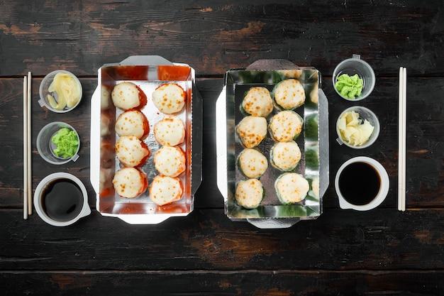 Saborosos rolos de sushi em caixas descartáveis, na velha mesa de madeira escura